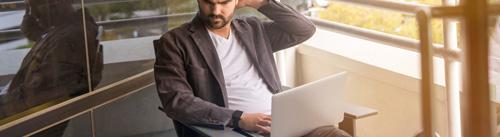 man working on his laptop while sitting